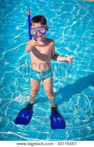 A little boy standing in a pool