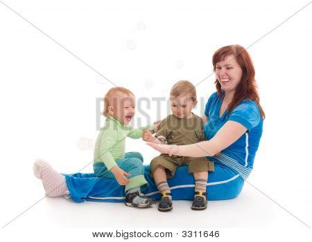 Mother With Sons Enjoy With Coloured Soap Bubbles