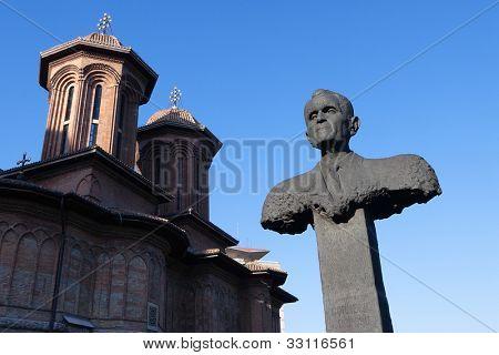 memorial bust of anti-communist Corneliu Coposu and  dome of Kretzulescu church in Bucharest, Romania