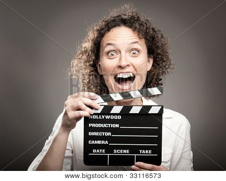 business woman holding a movie clapper board on a grey background