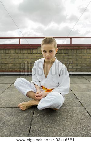 Judoka Teen Boy Sitting On The Roof (sky Background)