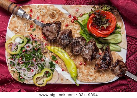 Fried beef kebab on a skewer with vegetables