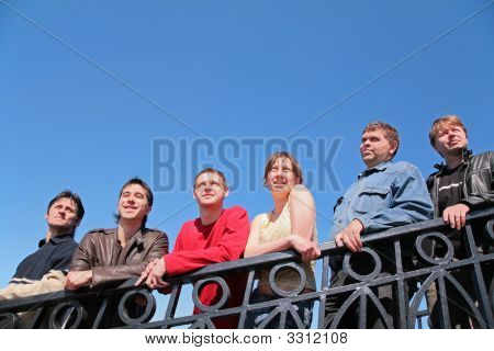 Group Of People Stand Leaning On Handrail