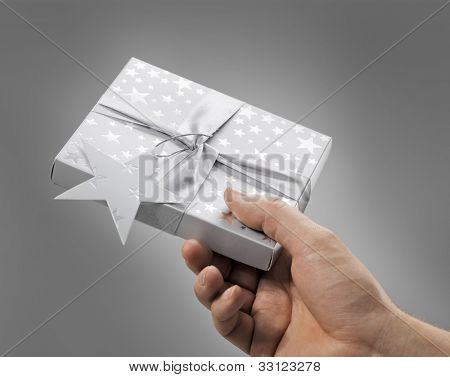 Man holding a gift box (contains a CD) in his hand.