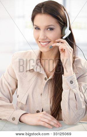 Portrait of pretty young dispatcher with headset, smiling.