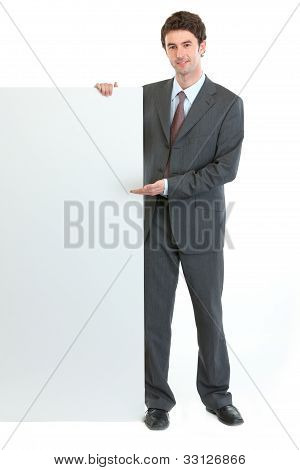 Modern Businessman Pointing On Blank Billboard
