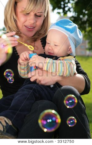 Mother With Child On Hands Is Started Up With Soap Bubbles