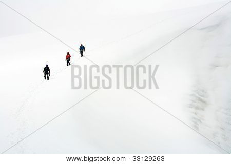 Team of three alpinists climbing a mountain during foggy weather