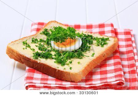 Crujiente rebanada de pan con mantequilla y perejil en una servilleta de cuadros roja