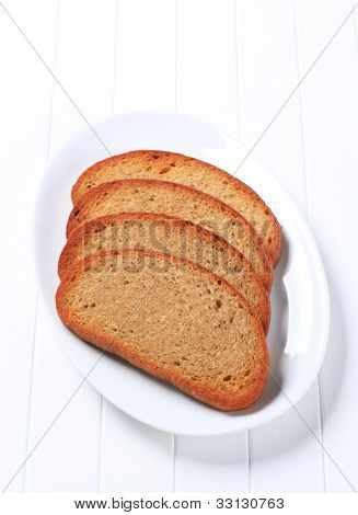 Four slices of bread on a white oval plate