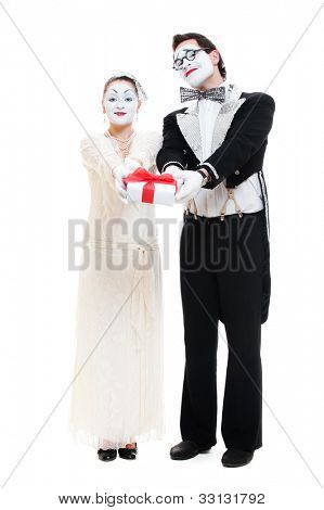 two funny mimes with gift box in studio on white background
