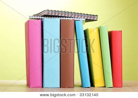 Books with stationery on wooden table on green background
