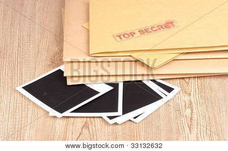 Envelopes with top secret stamp with photo papers close-up on wooden background