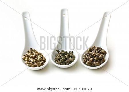 dry leaves of green tea in ceramic spoon