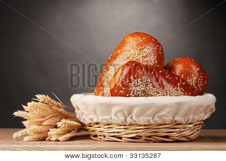 Baked bread in basket on wooden table on grey background