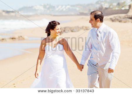 pareja de recién casados feliz caminar en la playa