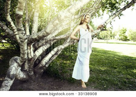 Pretty young woman in the garden under the sun