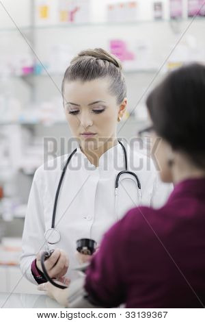 doctor checking blood pressure and heart rate in a hospital or in pharmacy with young female patient