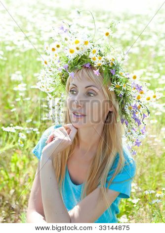 The happy young woman in a wreath from wild flowers in the field