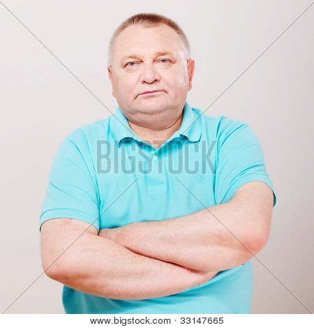 Confident middle aged man in shirt with crossed arms on his chest over white background