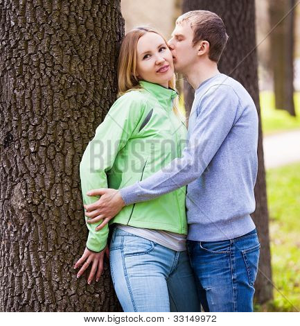 happy young kissing couple spending time outdoor on a summer day