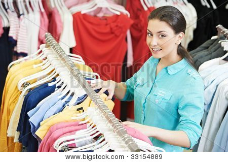 Young woman choosing shirt and blouse during clothing shopping at store