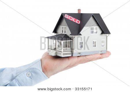 Conceito imóveis - mão segurando o modelo de arquitetura da casa, isolado