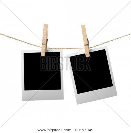 Two blank instant photos hanging on the clothesline. Isolated on white background.