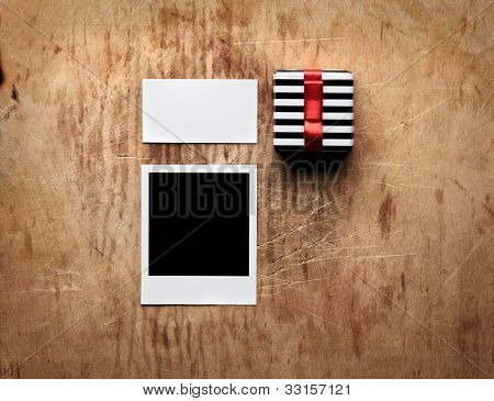 Gift box tied red bow and blank instant photo with white visit (gift) card on old wooden background.