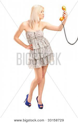 Full length portrait of a female holding a telephone and giving kisses isolated on white background