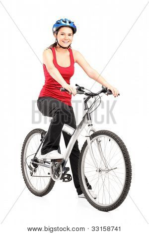 Female biker with helmet posing next to a bike isolated against white background