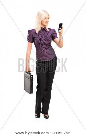 Retrato de cuerpo entero de una elegante joven sosteniendo un breifcase y hablando por un teléfono móvil iso