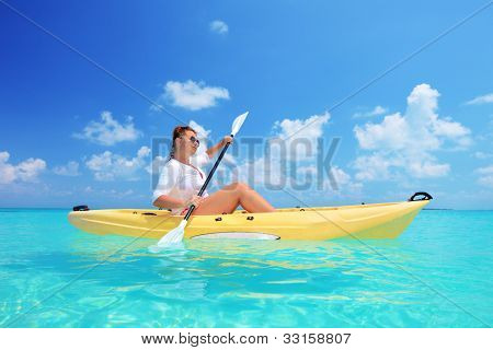 A woman kayaking on a sunny day, Kuredu island, Maldives, Lhaviyani atoll