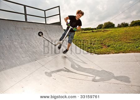 Boy Rides Scooter In The Halfpipe