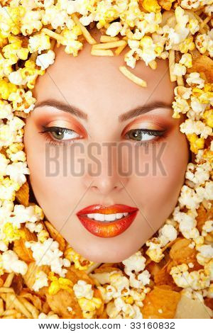 woman beauty face with unhealth eating fast food popcorn potato chips rusk frame