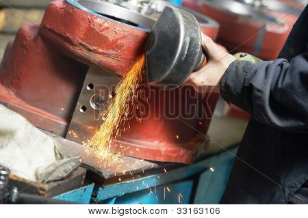 Close-up hand with power tool angular grinding machine at industrial machinery assembling and production line manufacturing workshop