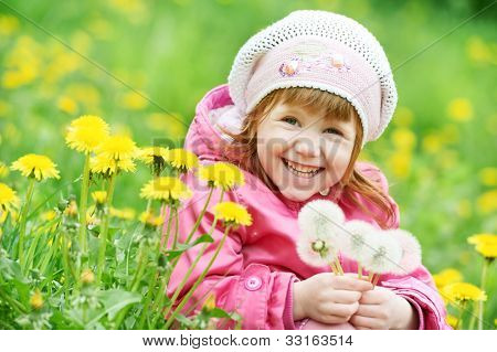 One little happy smiling girl with dandelion on summer or spring flower field