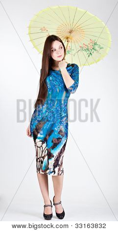 Brunette woman with chinese umbrella. Gray background