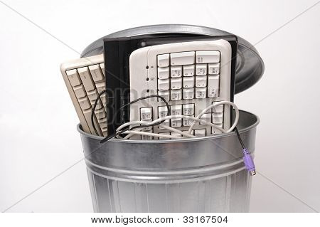 different computer parts and phone in trash can