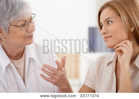 Senior mother and attractive daughter looking at each other with affection, talking, smiling.