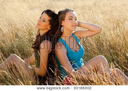 Zen moment between two young women in a wheat field in golden summer sunshine