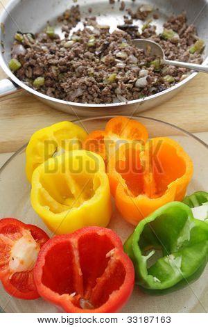 Un plato de pimientos esperando para rellenar y una sartén de picadillo de carne frita, cebolla, setas un