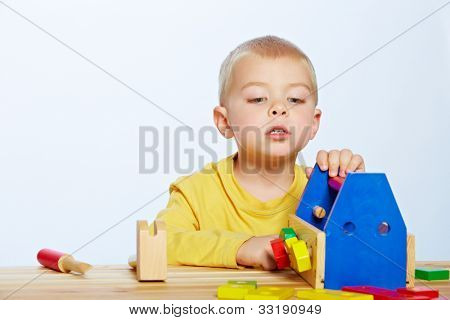 little 3 year old toddler boy with a wooden toolbox and tools over studio background