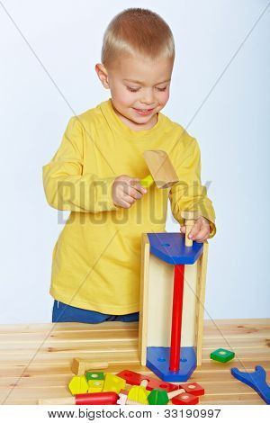 little 3 year old toddler boy with a toy wooden hammer and toolbox over studio background