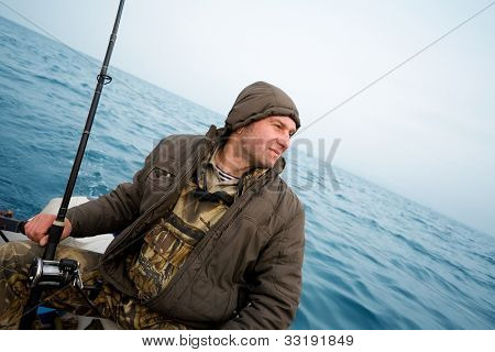 Angler fisherman catches a salmon trolling in the sea.