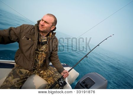 Fishing for salmon. Fisher holds a trolling rod.