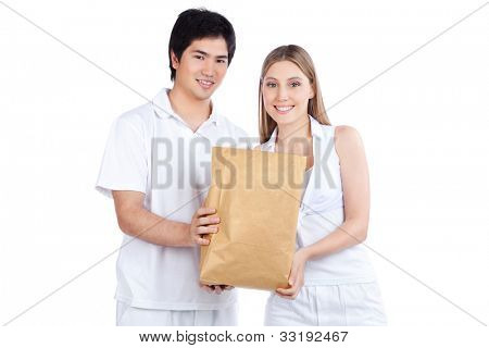 Portrait of young happy couple holding paper bag.