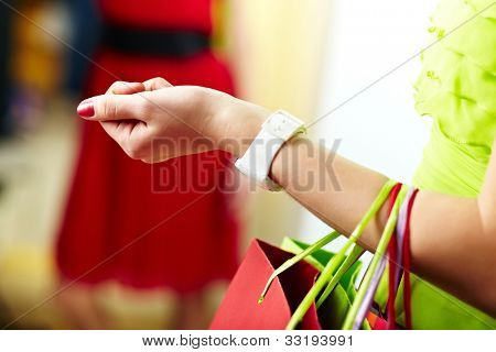 Image of shopaholic arm with colorful shopping bags