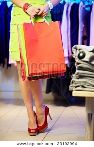 Image of shopaholic with shopping bags in clothing department