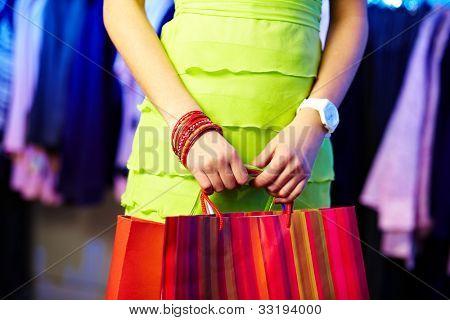 Imagem de mãos shopaholic com três sacos de compras